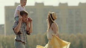 Portrait des parents avec leur fils dans la rotation de parc La mère monte à son mari pour embrasser son petit fils banque de vidéos
