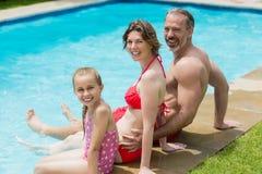 Portrait des parents et de la fille s'asseyant sur le poolside dans l'eau de piscine Photographie stock