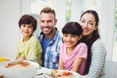 Portrait des parents et des enfants de mêmes parents de sourire à la table de salle à manger Photos stock