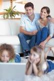 Portrait des parents observant leurs enfants à l'aide d'un ordinateur portable Images libres de droits