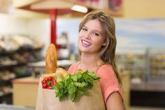 Portrait des produits alimentaires de achat assez de sourire de femme blonde image stock