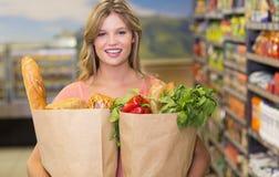 Portrait des produits alimentaires de achat de femme assez blonde Photos stock