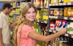 Portrait des produits alimentaires de achat de femme assez blonde Photo libre de droits