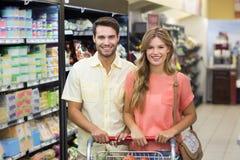 Portrait des produits alimentaires de achat de sourire de couples lumineux Image libre de droits