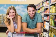 Portrait des produits alimentaires de achat de sourire de couples lumineux Images stock