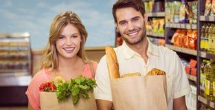 Portrait des produits alimentaires de achat de sourire de couples lumineux Photos libres de droits