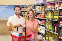Portrait des produits alimentaires de achat de sourire de couples lumineux utilisant le panier à provisions Images libres de droits