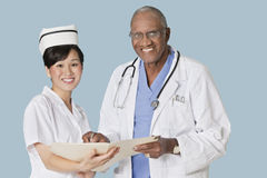 Portrait des professionnels heureux de soins de santé avec le rapport médical au-dessus du fond bleu-clair Photographie stock libre de droits