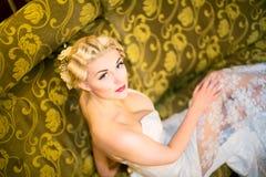 Portrait des schönen Mädchens im weißen Kleid auf Sofa Lizenzfreie Stockfotos