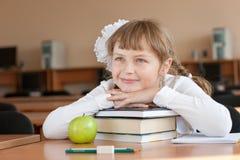 Portrait des Schulmädchens am Schuleschreibtisch Stockfotografie