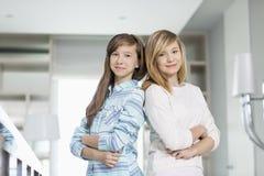 Portrait des soeurs mignonnes se tenant ensemble à la maison Image stock