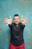 Portrait des sourires lumineux et des tractions d'un jeune homme les bras en avant photo stock