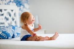 Portrait des spielerischen Kleinkindmädchens, das auf Bett sitzt Stockbild