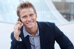 Portrait des stattlichen Geschäftsmannes, der Handy verwendet Lizenzfreie Stockfotos