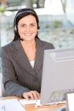 Portrait des tragenden Kopfhörers der Frau unter Verwendung des Computers Lizenzfreies Stockfoto