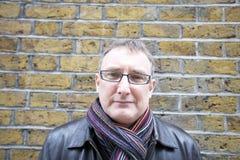 Portrait des verres de port d'un homme mûr avec l'écharpe contre le mur Image stock