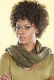 Portrait des verres de port d'une femme futée d'Afro-américain avec une étole ronde son cou au-dessus de fond coloré image libre de droits
