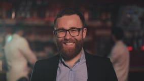 Portrait des verres de port de sourire d'homme attirant regardant la cam?ra dans un bar de barre ou de bi?re Concept de la jeunes banque de vidéos