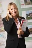Portrait des weiblichen Immobilienmaklers im Büro am Telefon lizenzfreie stockbilder