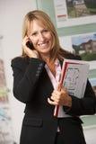 Portrait des weiblichen Immobilienmaklers im Büro am Telefon Stockbilder