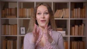 Portrait des yeux de roulement de joli professeur blond aux cheveux ondulés extrêmement s'amusant et étonnés à la bibliothèque banque de vidéos