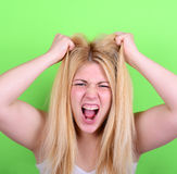 Portrait of desperate blond young woman pulling hair against gre Royalty Free Stock Images