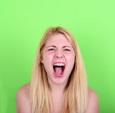 Portrait of desperate blond young woman screaming against green. This image is made in studio with model standing against colored backgrounds.Set of various Stock Photography