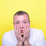Portrait of desperate man against yellow background Stock Image