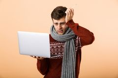 Portrait a desperate sick man dressed in sweater. And scarf isolated over beige background, browsing, holding laptop computer stock images