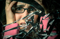 Oh no 7 years bad luck!. Portrait of a desperate woman looking at a broken mirror stock photo