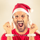 Portrait of a desperate young man with Santa Claus red hat. With handcuffs Royalty Free Stock Images