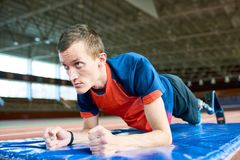 Motivated Handicapped Sportsman in Training. Portrait of determined amputee sportsman doing plank exercise training for paralympics in modern indoor stadium Royalty Free Stock Image
