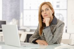 Portrait of determined businesswoman. Sitting at desk in office, looking at camera Royalty Free Stock Photography