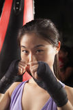Portrait of determined female boxer in fighting stance looking at camera Stock Images