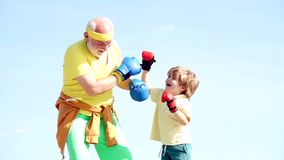 Portrait of a determined senior boxer with little boy child over blue sky background. Older - young man boxing. Handsome. Elderly man practicing boxing kicks stock footage