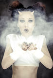 Portrait of devil woman blowing a white powder Royalty Free Stock Image