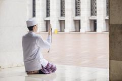 Devout Muslim man prays to the Allah. Portrait of devout Muslim man sitting in the mosque while praying to the Allah stock image