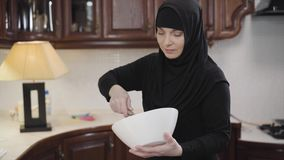 Portrait of diligent muslim woman in traditional hijab standing at kitchen and whisking. Young eastern lady cooking at