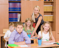 Portrait of diligent schoolgirl at lesson surrounded by her classroom Stock Image