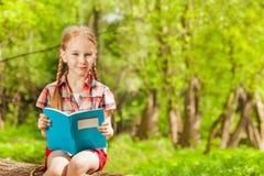 Portrait of diligent schoolgirl reading book Stock Photography