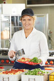 Portrait Of Dinner Lady Serving Meal In School Cafeteria Stock Photo