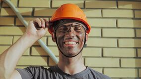 Portrait Dirty Building Worker on Background Brick Wall. Beautiful Caucasian Man in a Hard Hat Smiles. People Working Equipment.