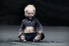 Portrait of dirty child on the black san beach. Funny portrait of smiling child with dirty face sitting and playing with fun on black sand sea beach before Stock Image