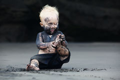 Portrait of dirty child on the black san beach. Funny portrait of smiling child with dirty face sitting and playing with fun on black sand sea beach before Royalty Free Stock Image