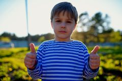 Portrait of dirty little boy in village with thumbs up Royalty Free Stock Images