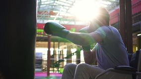 Portrait of a disabled man in a wheelchair, who beats a punching bag in the gym.Close up. Portrait of a disabled man in a wheelchair in Boxing gloves.He hits the stock footage