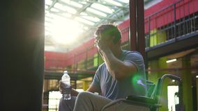 Portrait of a disabled man in a wheelchair drinking water after training in the gym.Close up. Portrait of a disabled Man in a wheelchair drinking water from a stock video