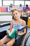 Portrait of disabled school girl reading book in library Stock Images