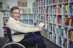 Portrait of disabled school teacher holding book in library Royalty Free Stock Image
