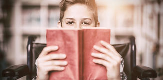 Portrait of disabled schoolboy holding book in library Royalty Free Stock Images